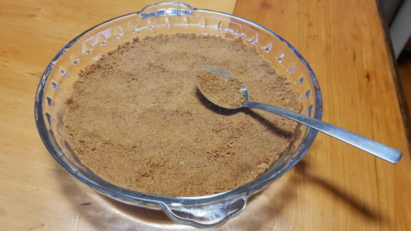 Pressing banoffee pie base into a glass pie dish