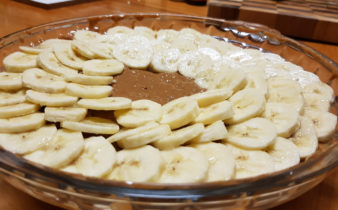 Bananas arranged on top of caramel layer of banoffee pie.