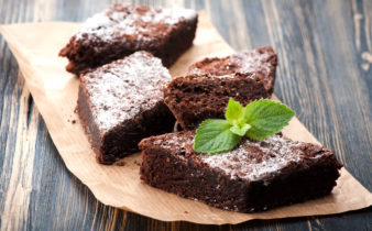 Finish chocolate brownie with raspberry, completed with a sifting of icing sugar